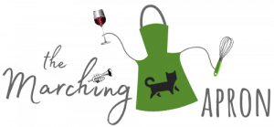 The Marching Apron logo with green apron holding a whisk in one tie and a glass of red wine in the other